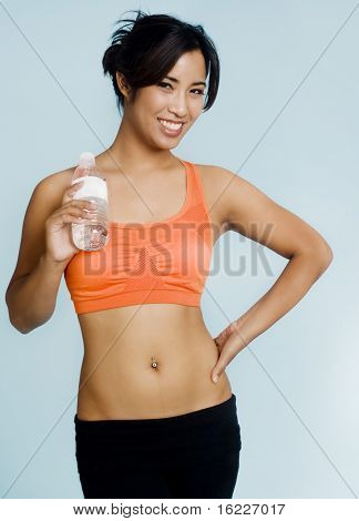 Beautiful athletic sporty girl drinking water
