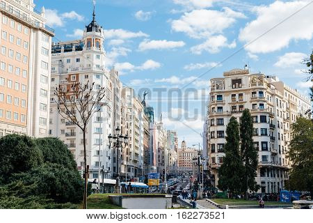 Madrid Spain - November 13 2016: Gran Via in Madrid. It is an ornate and upscale shopping street located in central Madrid. It is known as the Spanish Broadway. Sunny day
