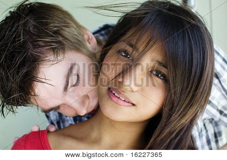 Young couple embrace and kiss in candid happy cute romantic natural moment