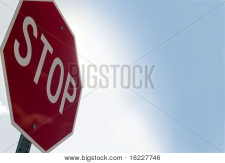 Stop sign background with blue and white bight sky background for copy text.