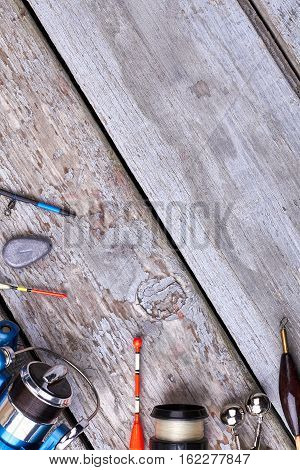 Fishing tackle on wooden backdrop. Reel, line and bobbers. Fishing as sport.