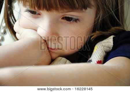 Candid natural shot of little girl in quiet moment of deep thought