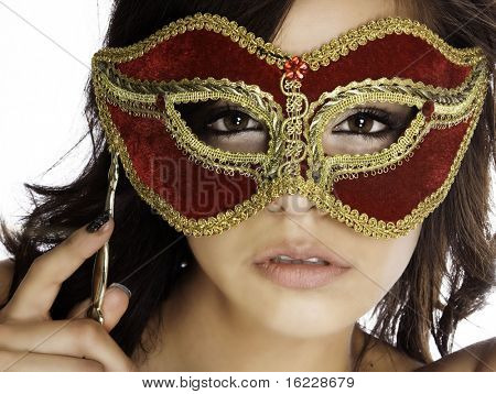 Beautiful mysterious woman's face behind ornate red and gold mask