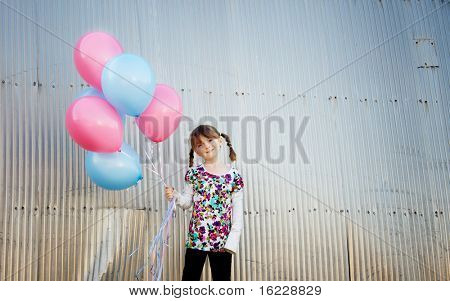 Pretty little girl with pigtails holding a bunch of balloons.  Image color toned.