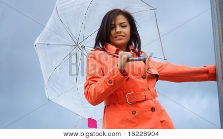Beautiful young happy vibrant smiling young woman wearing an orange tench coat and umbrella on a cloudy rainy day.