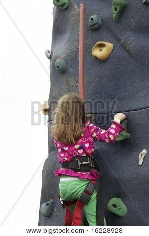 Little girl climbing rock wall at festival event