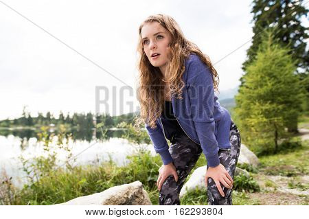 Beautiful young woman in blue sweatshirt at the lake in green nature, breathing hard after running outside