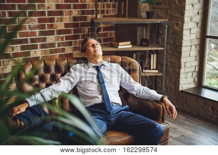 Exhausted male businessperson is freely sitting on couch. He is relaxing