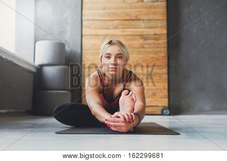 Young slim blond woman in yoga class making asana exercises. Girl do sitting forward bend pose. Healthy lifestyle in fitness club. Stretching