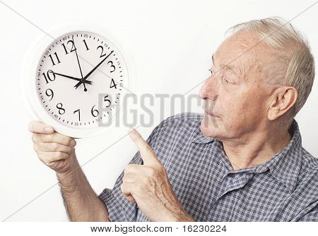 Mature older man looking and pointing at clock.