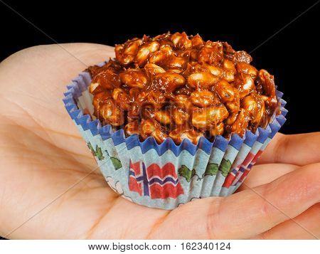 Puffed Rice Chocolate Cake In Paper Cup With Norwegian Flag, In Palm, Towards Black