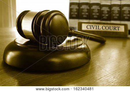 Judge's Civil Court gavel on a desk with law books