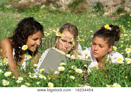 3 young women reading in a meadow