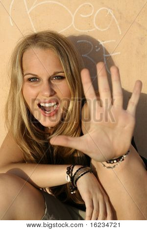 Girl holding hand up with palm towards camera