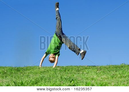 happy child doing cartwheel on hill