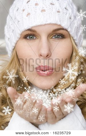 winter woman blowing a gift os snow to the camera