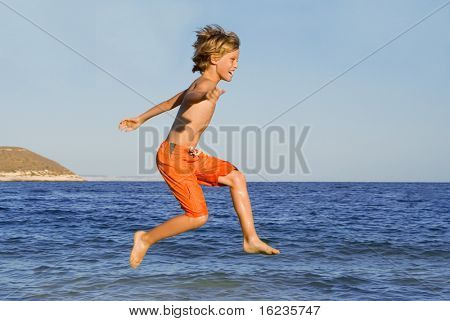 happy boy jumping on vacations(some motion blur on limbs)