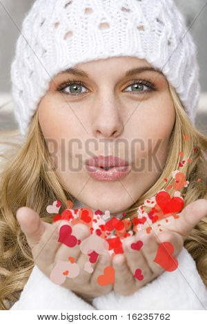 young woman blowing fantasy hearts to her valentines