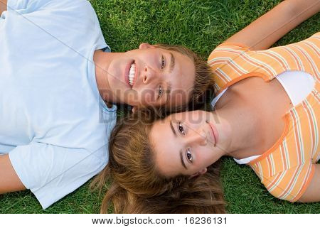 happy teenage boy and girl laying on grass