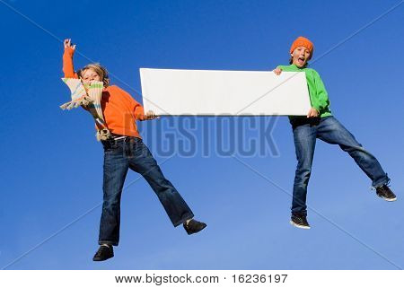 happy autumn boys jumping with blank sign