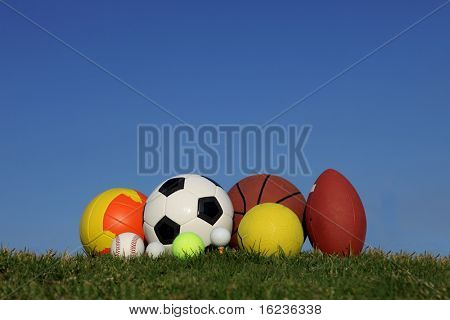 different children's sports balls outside on lawn