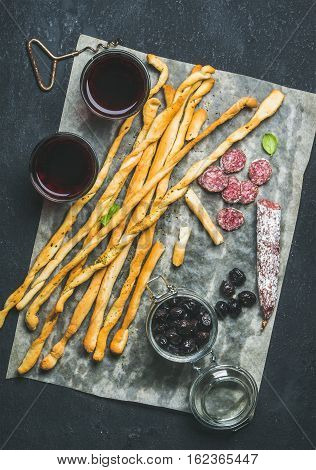Wine and appetizers set. Italian Grissini bread sticks, dry cured pork meat sausage, black olives in jar and red wine in glasses over dark stone background, top view