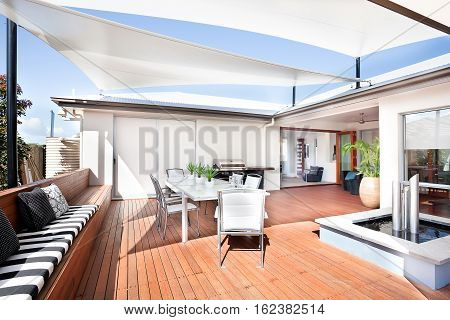 This patio area has a wooden floor and a long bench attached to it there are some small mattresses and pillows on it. A white table and chairs are under the creative roof design there is a new kind of water pond with silver tubes