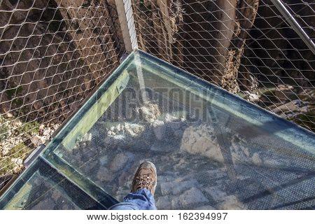 Trekking shoes over glass footbridge at Caminito del Rey path Malaga Spain