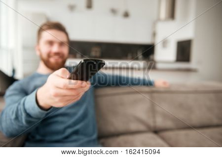 Photo of young man holding remote control while watching TV. Focus on remote control.