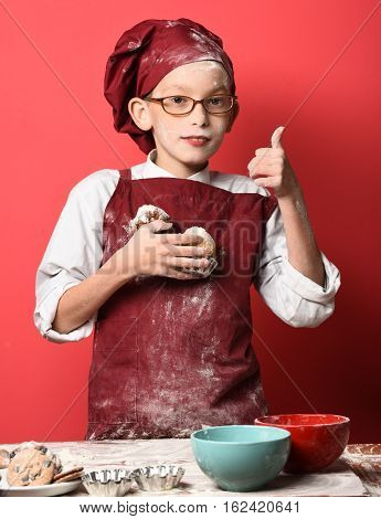 young boy cute cook chef in uniform and hat on stained face flour with glasses standing near table with colorful bawls and holding tasty chocolate cakes on red studio background