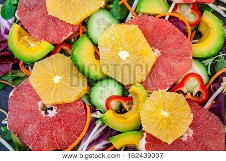 Vegetable Vegan background: lettuce carrots peppers avocado sprouts pepper cucumber avocado orange grapefruit. Top view dark slate. Love for a healthy raw food concept.