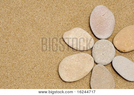flower made with stones on a sand background