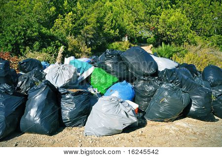 a pile of full garbage bags in a dump