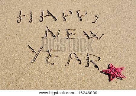 frase feliz ano novo, escrito na areia