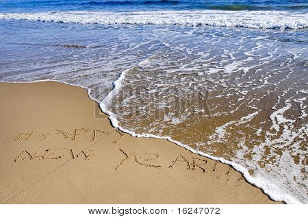 happy new year written in the sand of a beach