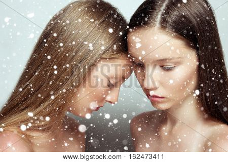 winter christmas people beauty concept- studio portrait of two young beautiful women. Beauty Woman face Portrait. Beautiful Spa model Girl with Perfect Fresh Clean Skin. over snow background