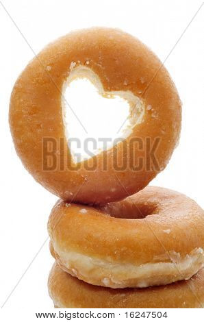 a pile of donuts one with the hole shaped as a heart on a white background