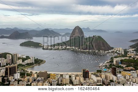Classical beautiful aerial view of the Sugarloaf mountain, boats floating in Botafogo Bay and cityscape of Rio de Janeiro, Brazil at dull day