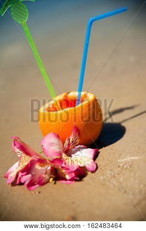 Vacation Concept - Orange With Coctail Straw And Exotic Flowers On The Beach