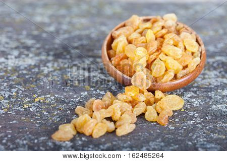 Yellow raisins or sultanas in a small wooden bowl on a vintage, old board background