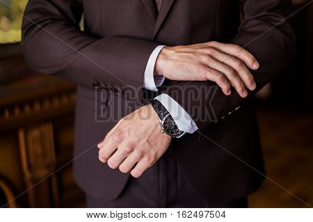 watch on a man's hand the fees of the groom wedding preparation preparation for work putting the clock on the hand fasten clock watch time man's style sense of style correcting sleeves