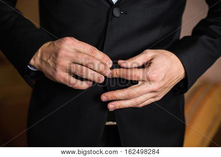 correct button on jacket hands close-up dressing man's style correcting sleeves ready for work preparing for the wedding