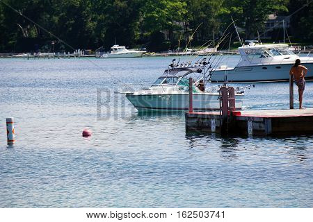 HARBOR SPRINGS, MICHIGAN / UNITED STATES - AUGUST 3, 2016: A fishing boat sails near the raft at the Zorn Park Public Beach near downtown Harbor Springs.