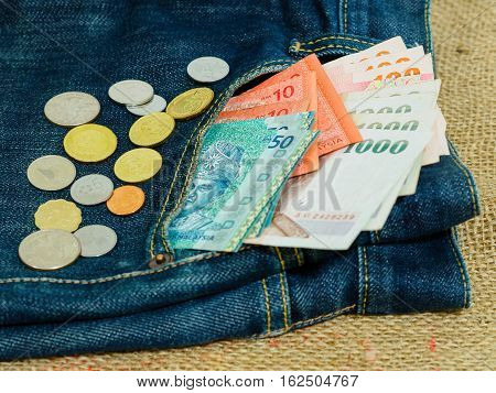 Blue jeans pocket with Malaysian and Thai banknotes and coins on brown hemp sack texture background. Money for travel and shopping