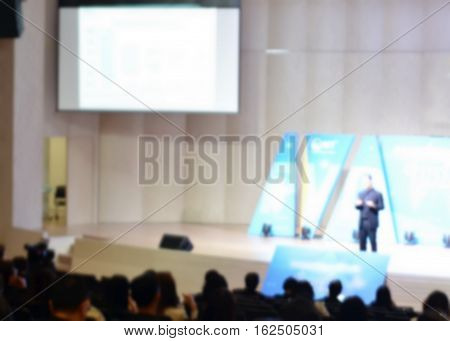 Speaker giving a talk at business meeting and audience in the conference hall with copy space on white screen blur background, business conference and presentation.