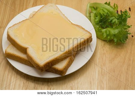 Breads and sweetened condensed milk in a white plate on a wooden board