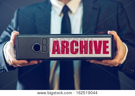 Businessman with archive files in document ring binder paperwork and legal corporate papers collected