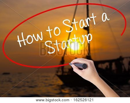 Woman Hand Writing How To Start A Startup With A Marker Over Transparent Board