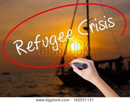Woman Hand Writing Refugee Crisis With A Marker Over Transparent Board