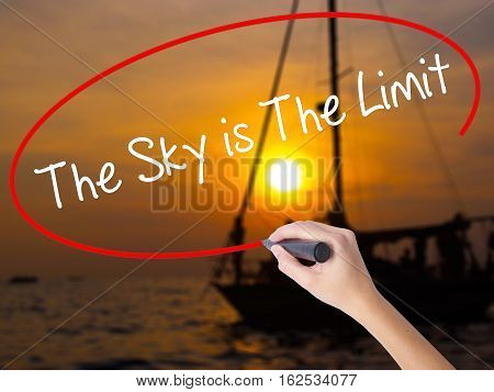 Woman Hand Writing The Sky Is The Limit  With A Marker Over Transparent Board